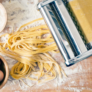 fresh pasta and pasta machine on kitchen table